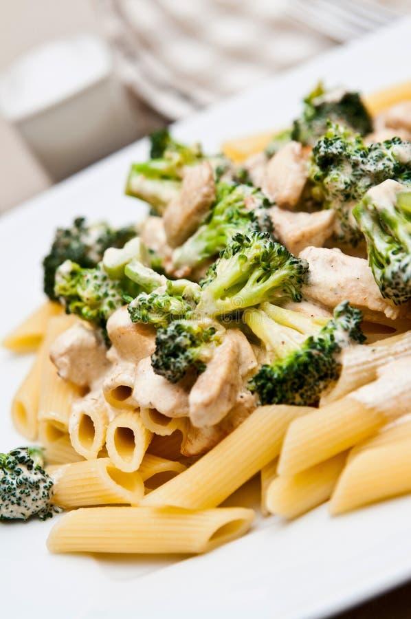 Deegwaren met kip en broccolischotel stock foto