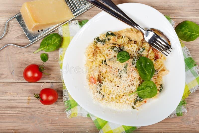Deegwaren met kippenvlees, spinazie, tomaten, roomsaus en kaas stock foto