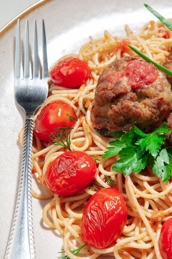 Deegwaren met vleesballetjes en tomatensaus Verfraaid met greens en geroosterde kersentomaten In de originele plaat Op de plaat l royalty-vrije stock fotografie