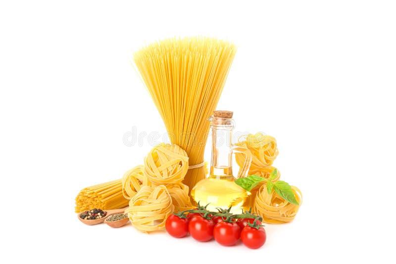 Deegwaren, olijfolie, tomaten en kruid op witte achtergrond worden geïsoleerd die stock afbeelding