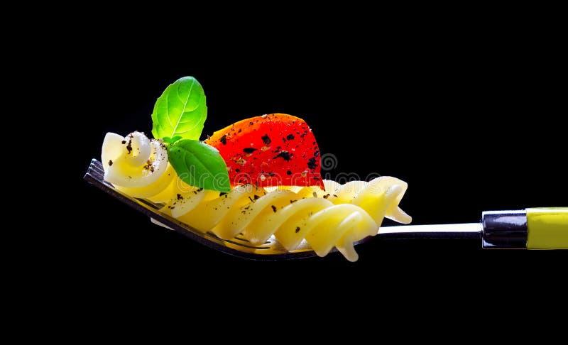 Deegwaren, tomaat en basilicum op een vork, op zwarte wordt geïsoleerd die royalty-vrije stock foto's