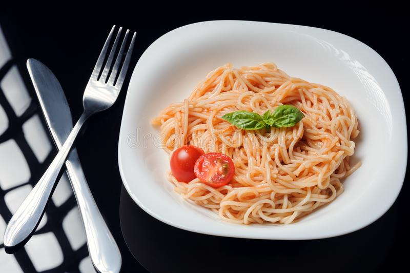 Deegwaren in tomatensaus op een zwarte achtergrond royalty-vrije stock afbeelding