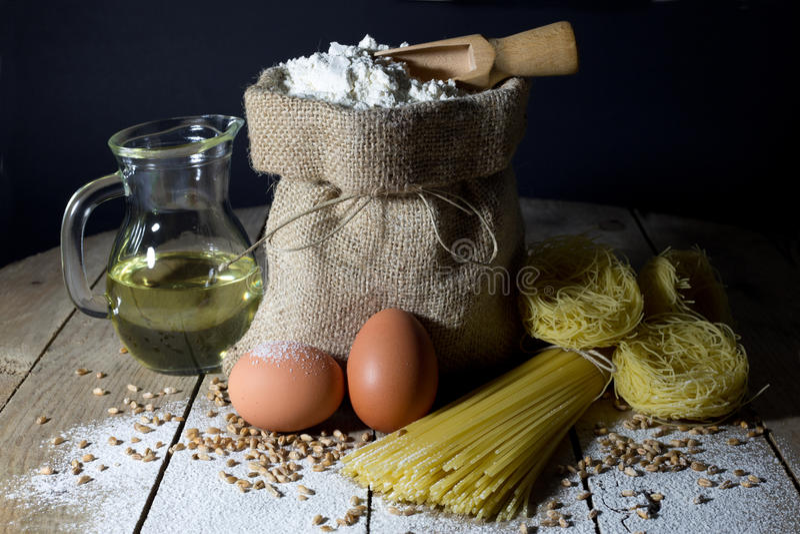 Deegwaren, Twee die Eieren, Jutezak met Bloem worden gevuld, Houten Lepel en Olive Oil in Glasfles op Houten Lijst, Zwarte Achter stock afbeeldingen
