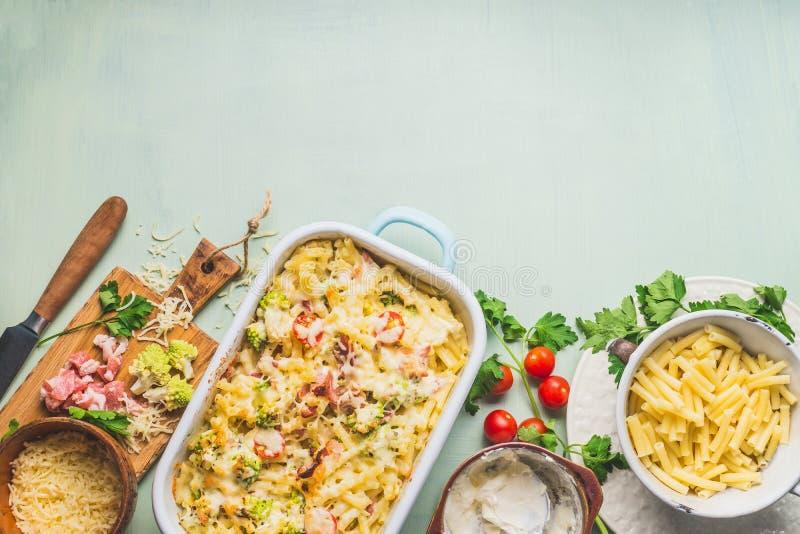Deegwarenbraadpan met romanescokool en ham in romige saus, op de achtergrond van de keukenlijst met ingrediënten, hoogste mening, stock afbeelding