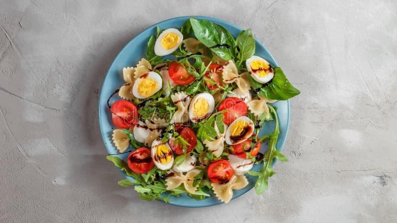 Deegwarensalade met kwartelseieren, tomaten, rucola, mozarella en basilicum stock foto
