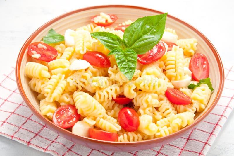 Deegwarensalade met tomaten, olijven, mozarella en basilicum Italië stock afbeelding