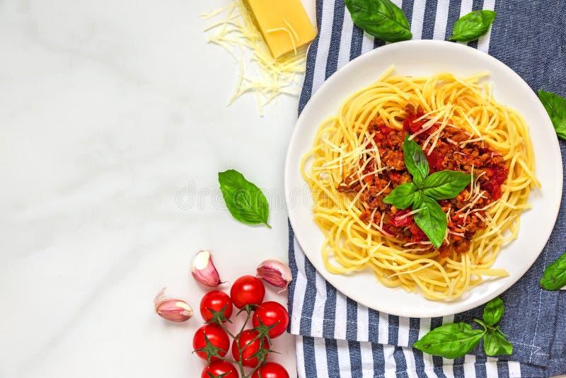 Deegwarenspaghetti bolognese op een witte plaat op keukenhanddoek over witte marmeren lijst Gezond voedsel Hoogste mening stock fotografie