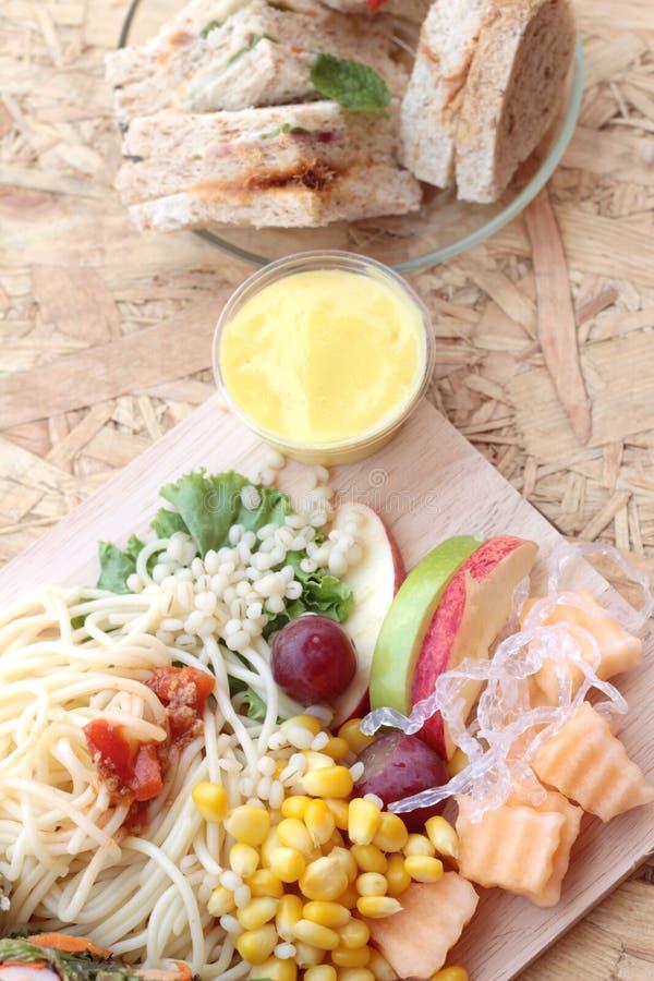 Deegwarenspaghetti met het fruit van de salademengeling en broodsandwich stock afbeeldingen