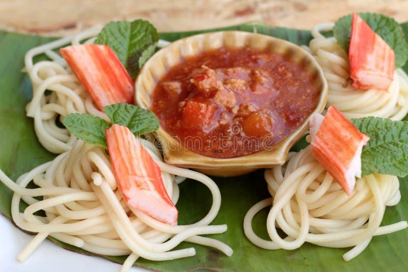 Deegwarenspaghetti met krabstokken en saus stock foto's