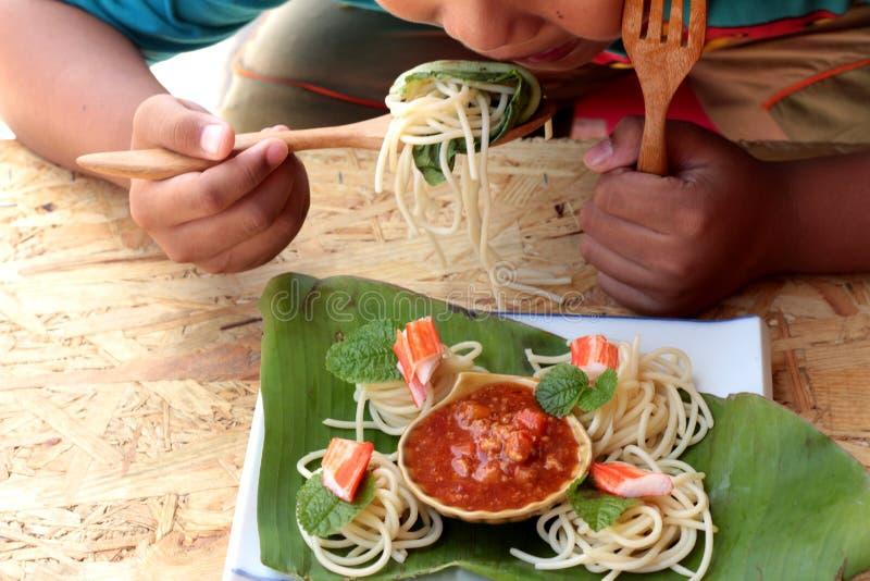 Deegwarenspaghetti met krabstokken en saus stock foto