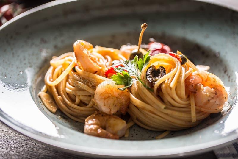 Deegwarenspaghetti op plaat en pan met garnalentomatensaus toatoes en kruiden Italiaanse of mediterrane keuken royalty-vrije stock foto's