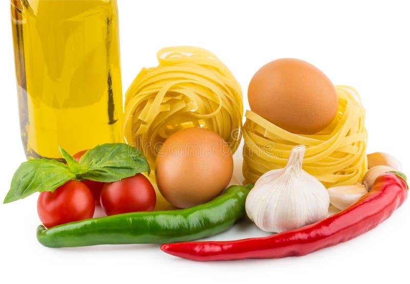 Deegwarentagliatelle, fles olijfolie, tomaten, knoflook, Spaanse peper royalty-vrije stock foto's