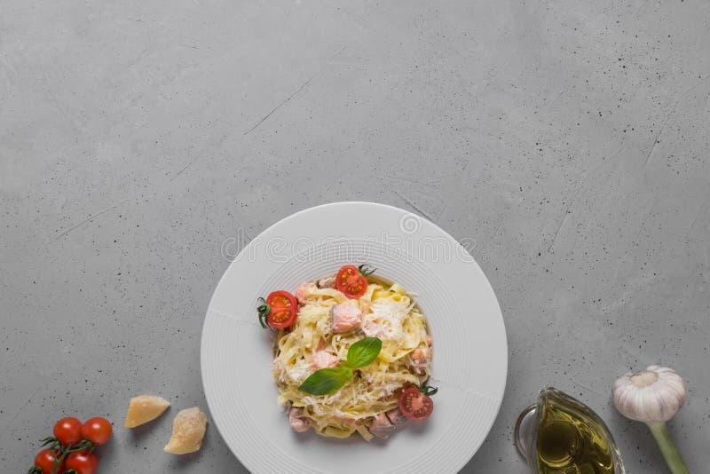 Deegwarentagliatelle met forel en room in witte plaat en ingrediënt op lichte achtergrond Heerlijke mediterrane lunch royalty-vrije stock afbeeldingen