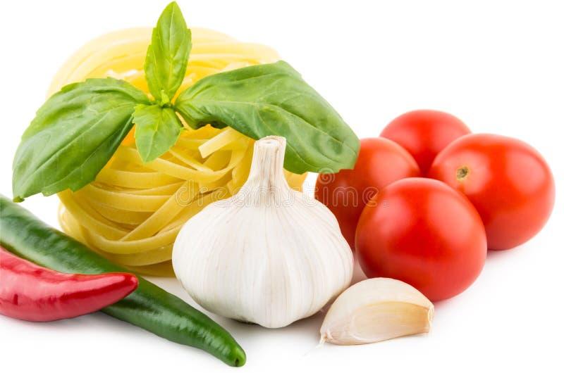 Deegwarentagliatelle, tomaten, knoflook, Spaanse peperpeper en basilicum stock foto's