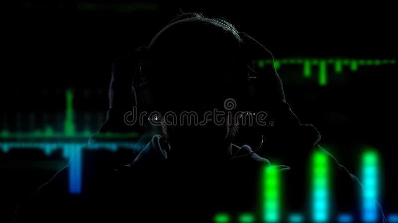Deejay in hoofdtelefoons die en muziek op de achtergrond van equalisergevolgen spelen mengen stock afbeelding