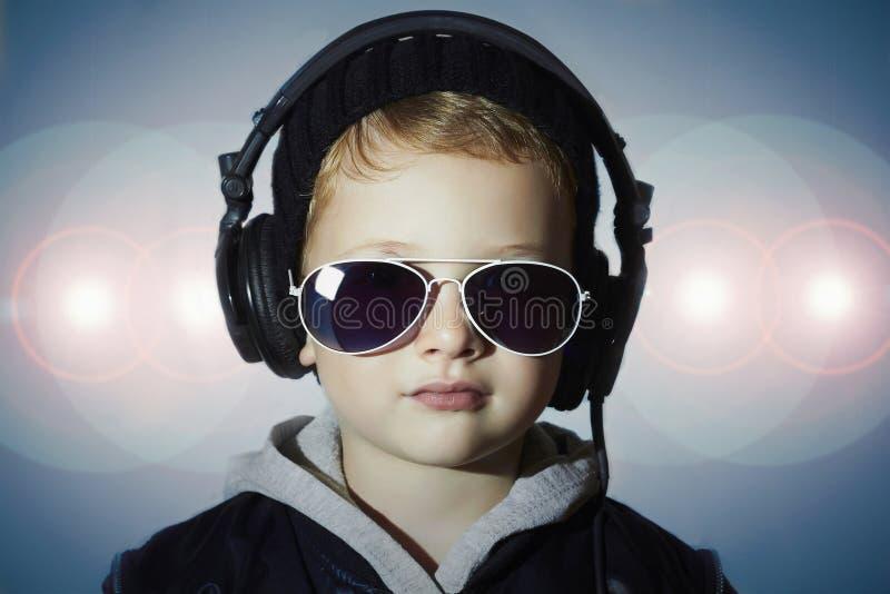 Deejay Ittle grappige jongen in zonnebril en hoofdtelefoons Het luisteren van het kind muziek stock fotografie