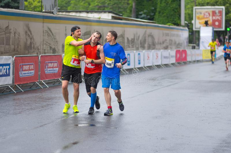 Deelnemers die andere kerel helpen die bewustzijn tijdens van ` Interipe Dnipro Halve Marathonrace ` losmaakt stock fotografie
