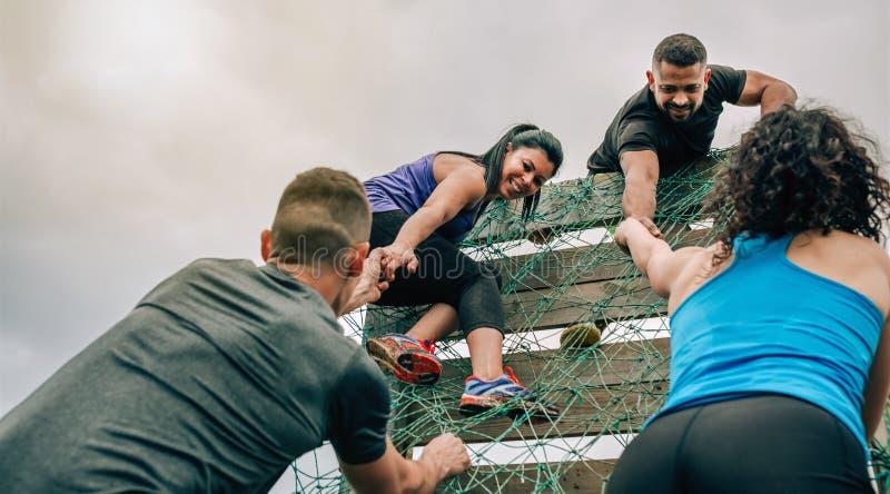 Deelnemers in hinderniscursus netto beklimmen stock afbeelding