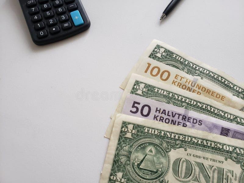 Deense bankbiljetten, Amerikaanse dollarrekeningen, calculator en zwarte pen op witte achtergrond stock afbeelding