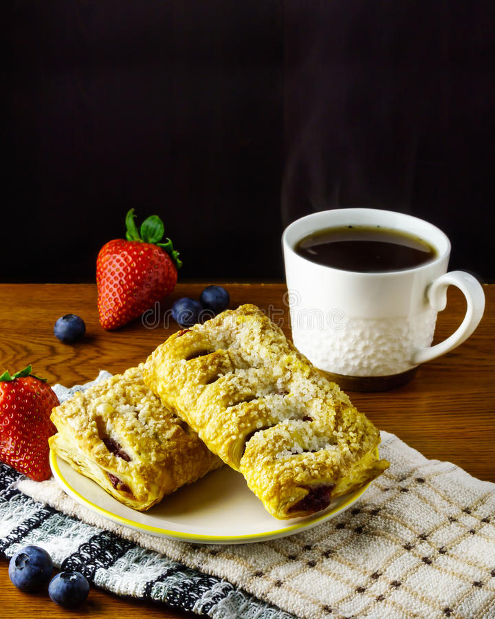 Deense broodjes met starwberry bosbes en koffie stock foto's