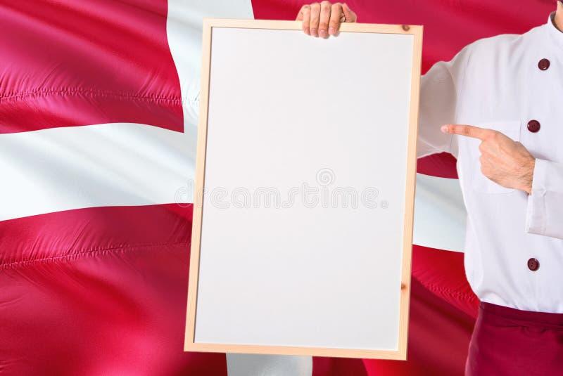 Deense Chef-kok die leeg whiteboardmenu op de vlagachtergrond van Denemarken houden Kok die eenvormige richtende ruimte voor teks stock fotografie