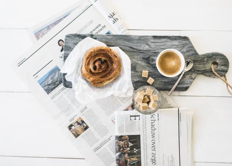 Deense koffie breadroll met koffie en krant stock afbeelding