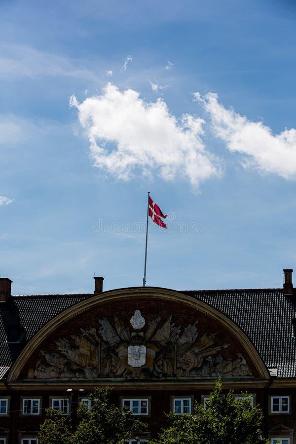 Deense vlag in Kopenhagen over een blauwe lucht stock foto's