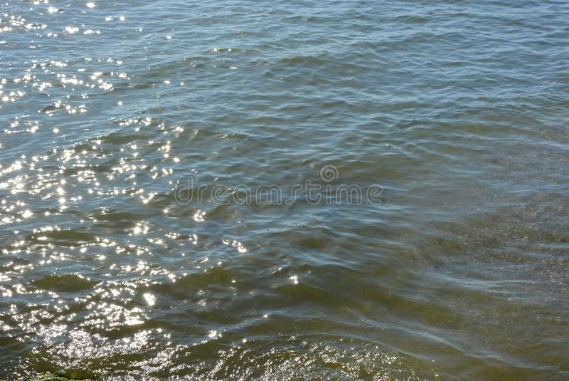 Deep blue black seas with small waves and small golden and bright sun reflections on a sea background stock image