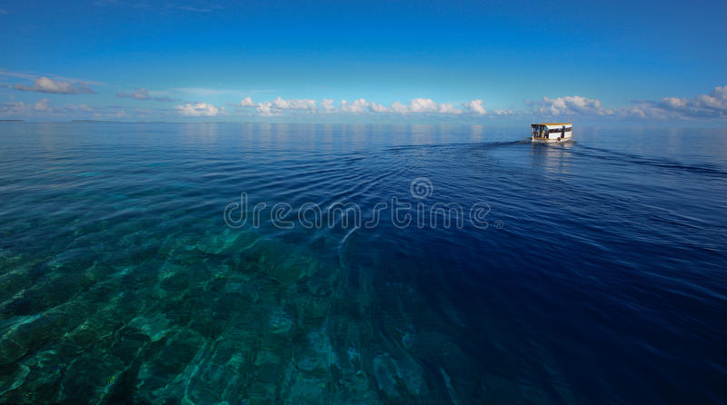 Deep blue ocean and boat. Deep blue ocean, boat and clouds on the horizon stock images