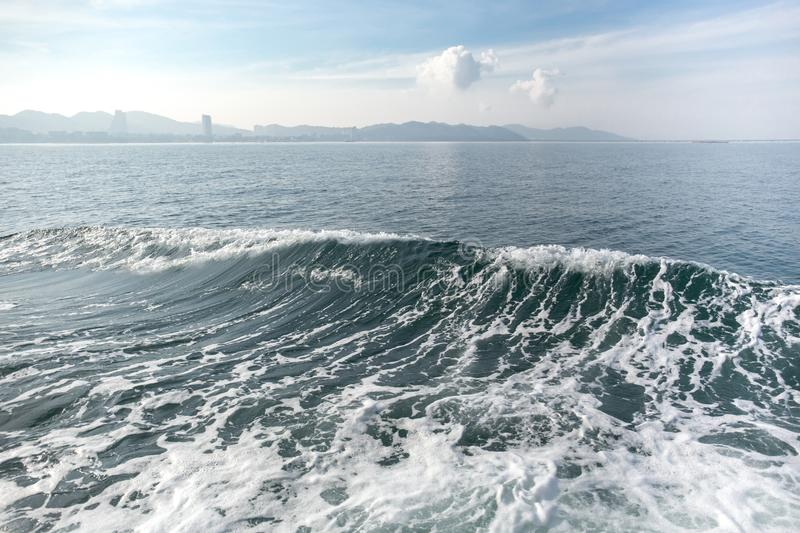 Deep blue ocean wave with mountain and sky royalty free stock images