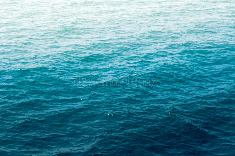 Deep blue sea water wave suface with sun reflection. stock photography