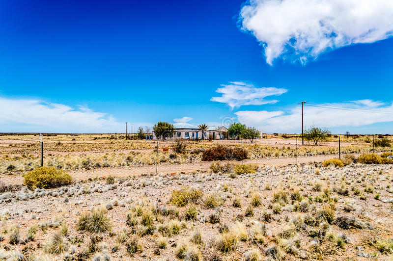 Deep blue skies. A lonely famhouse in an arid region framed by deep blue summer skies stock images