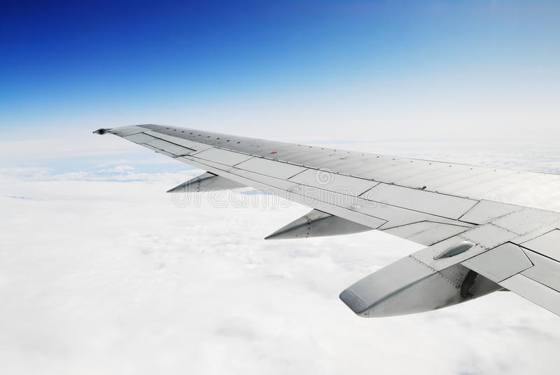 Deep blue sky, white clouds and airplane wing. Bright image of airplane wing stock image