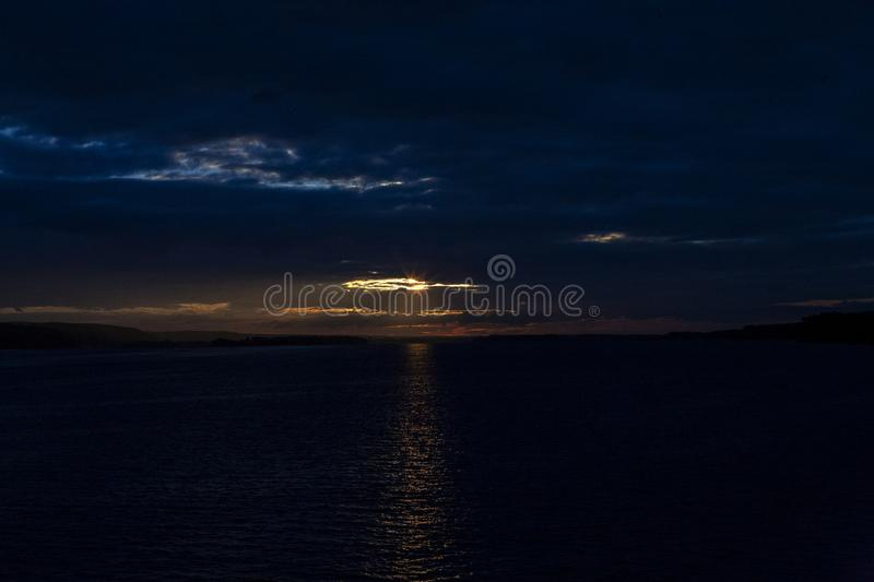 Deep blue sunset sky with orange sun rays and big cumulus clouds above a water. stock photos