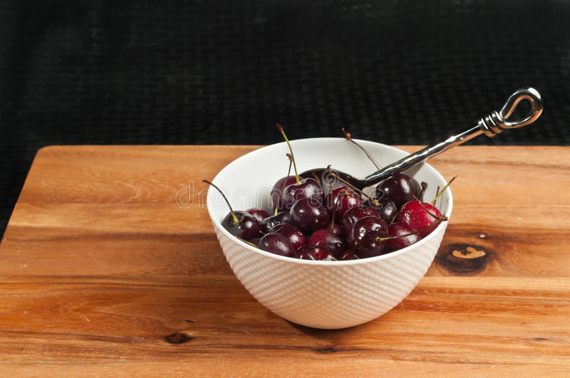 Deep bowl of organic cherries stock image