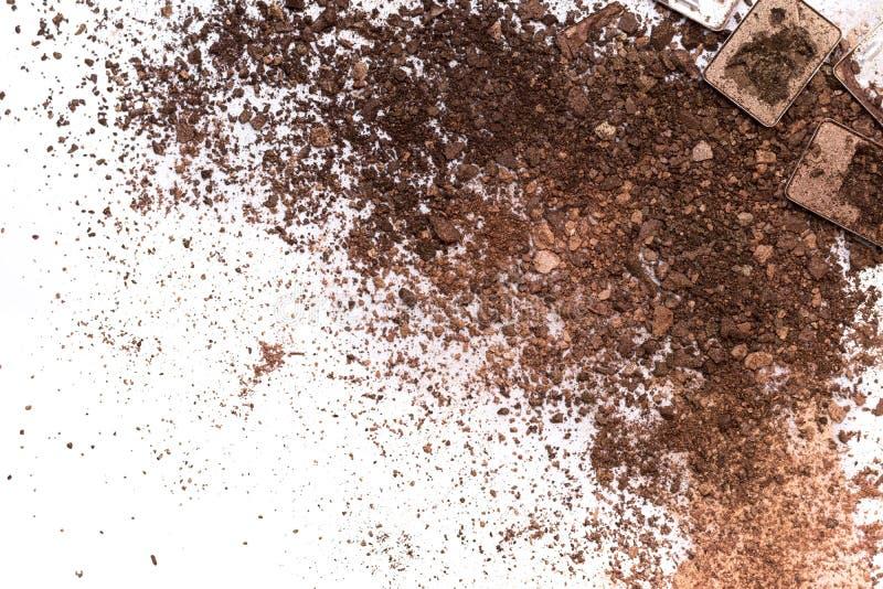 Deep brown crumbled eye shadow isolated on white background.Broken brown eyeshadow palette isolated on a white background royalty free stock images