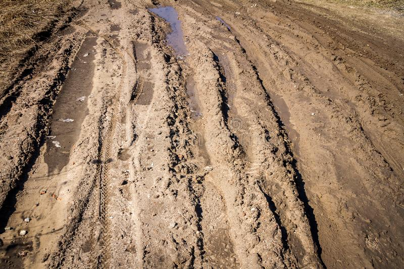 Deep car rut on a dirt road. Empty countryside dirt wet road royalty free stock photo