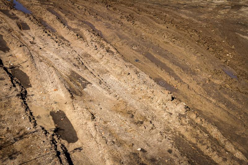 Deep car rut on a dirt road. Empty countryside dirt wet road stock image