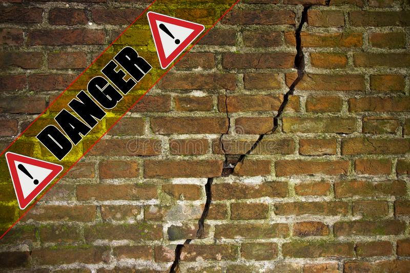 Deep crack in old damaged damp brick wall - concept image with danger text written on it.  stock photo