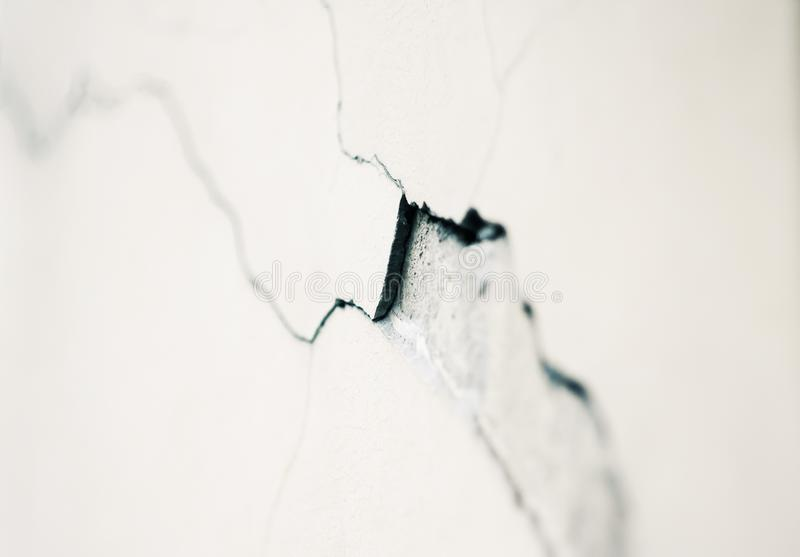 Deep crack in the plaster on a white wall stock photography