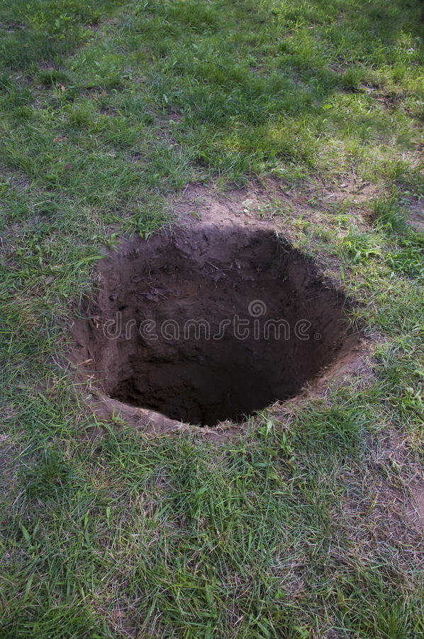 Deep dirt hole in ground. Or lawn stock image