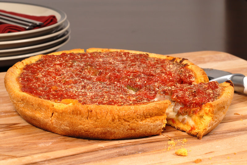 Deep dish pizza with a piece cut out stock photography