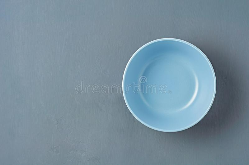 Deep empty ceramic bowl of blue color lies on dark concrete background. Space for text. Top view royalty free stock photography