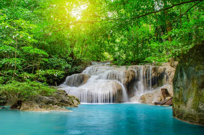 Deep forest waterfall at Erawan waterfall, beautiful waterfall with sunlight rays in deep forest, Erawan National Park. In Kanchanaburi, Thailand royalty free stock photo