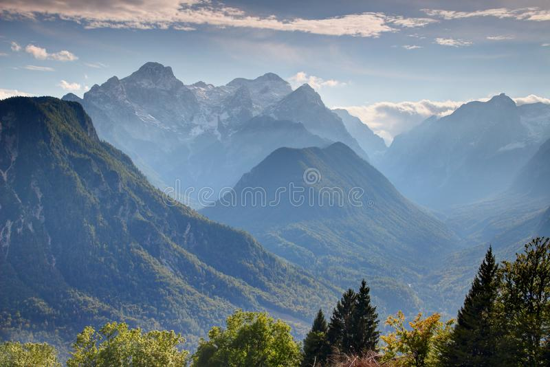 Deep forested valleys with snowy peaks in Julian Alps Slovenia. Steep forested walls of Vrata, Kot and Sava valleys in autumn haze with snowy Triglav and Rjavina stock photos