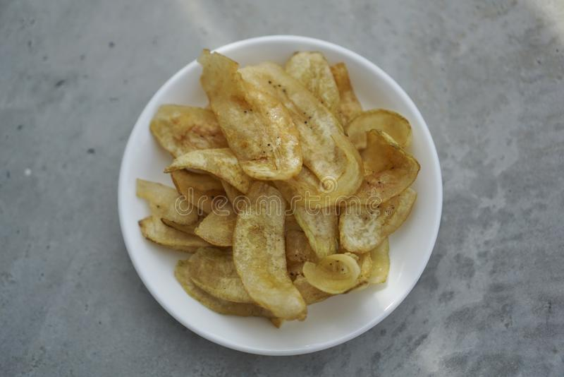 Deep fried banana chips on white plate. royalty free stock photography