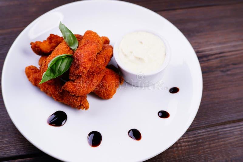 Deep-fried battered chicken nuggets with sauce. Deep-fried battered chicken nuggets with garlic sauce, popular beer snack. Oktoberfest food, pub, bar, restaurant stock images