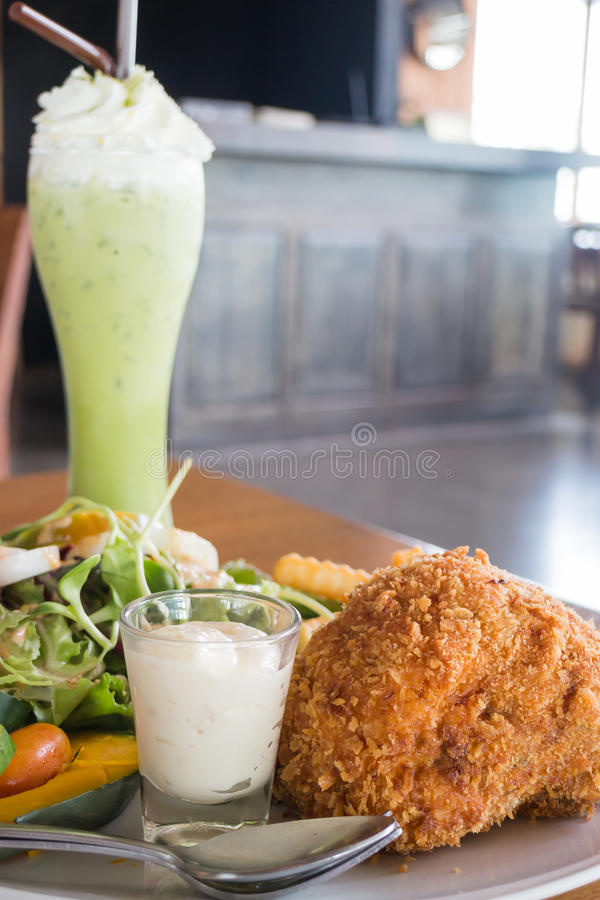 Deep fried chicken meat and ice green tea royalty free stock photography