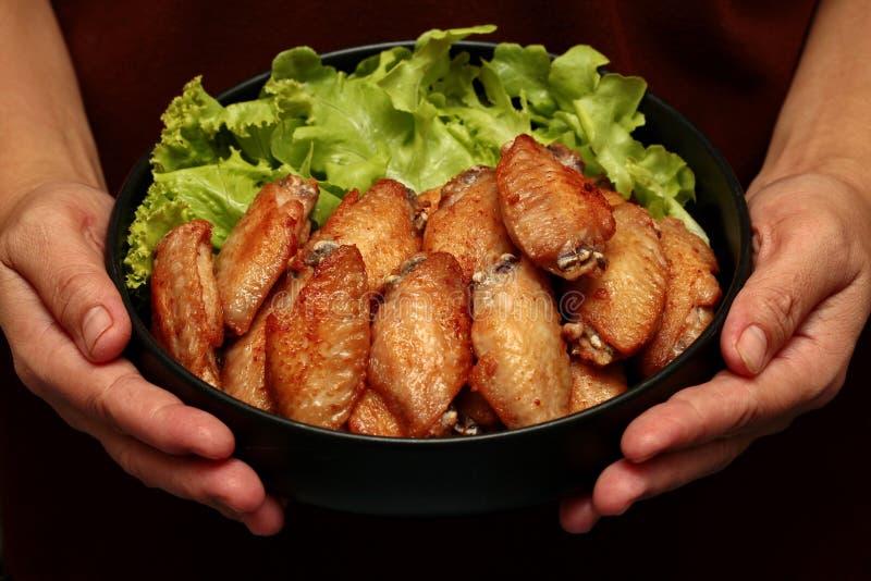Deep fried chicken wings topped green oak. stock image
