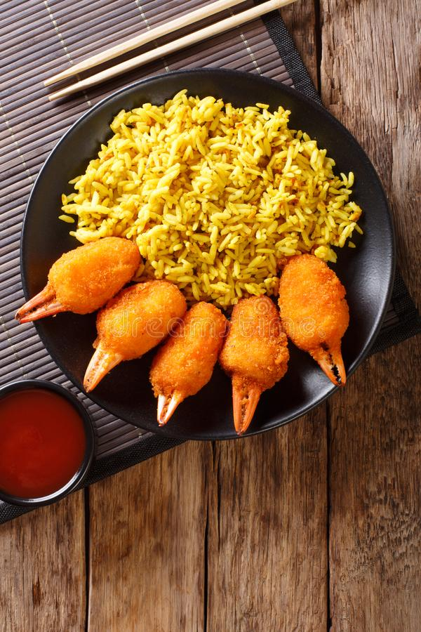 Deep fried crab claws in breadcrumbs of surimi with spicy yellow. Rice close-up on a plate on a table. Vertical top view from above stock images